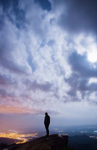 person man standing on cliff with cityscape view under cloudy sky nature