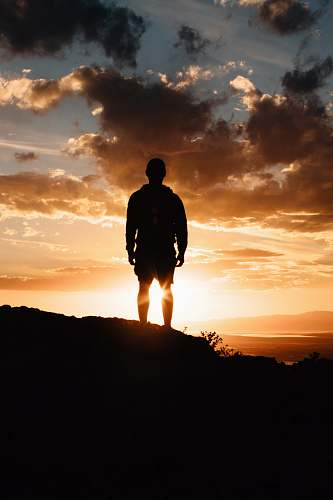 person man standing on mountain during sunset people