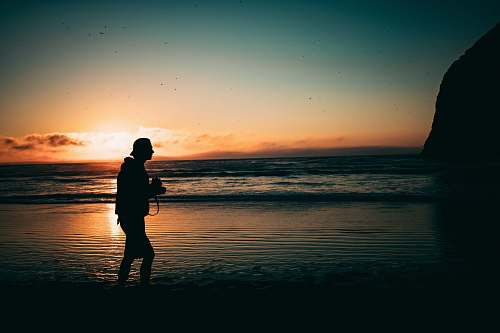 person man walking on seashore at golden hour people