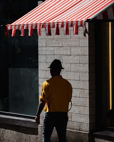 person man walking under red and white striped awning during daytime people
