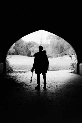 person person standing inside tunnel black-and-white