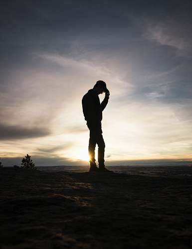 person silhouette man standing holding cap during sunset people