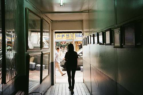 person silhouette of a woman walking at the corridor people