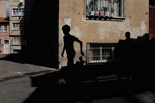 person silhouette of boy running near brown concrete building during daytime people