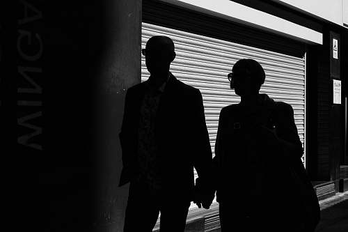 people silhouette of man and woman walking inside building black-and-white