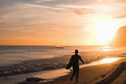 person silhouette of man carrying surfboard running on shore people