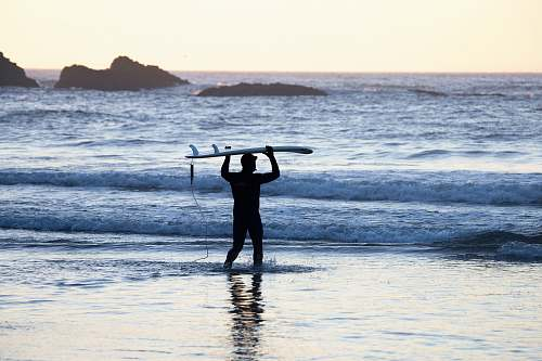 person silhouette of man holding surfing board in seashore during daytime people