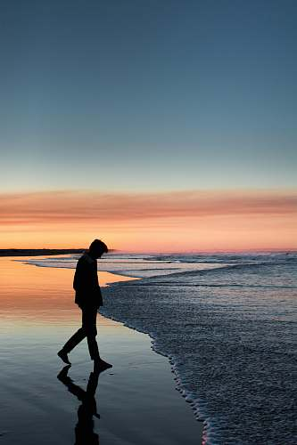 person silhouette of man walking on seashore under orange sky standing