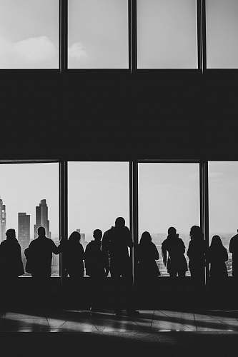 person silhouette of people looking at windows black-and-white