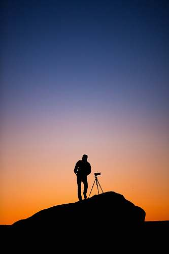 person silhouette of person standing beside DSLR camera with stand at sunset tripod