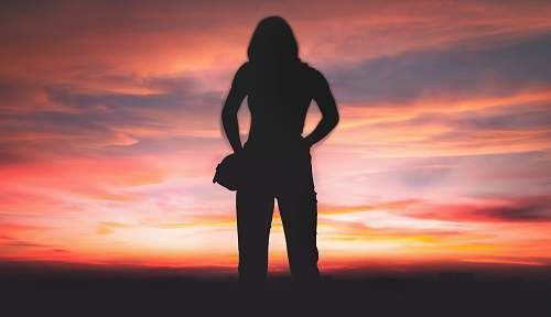 person silhouette of person standing during golden hour standing