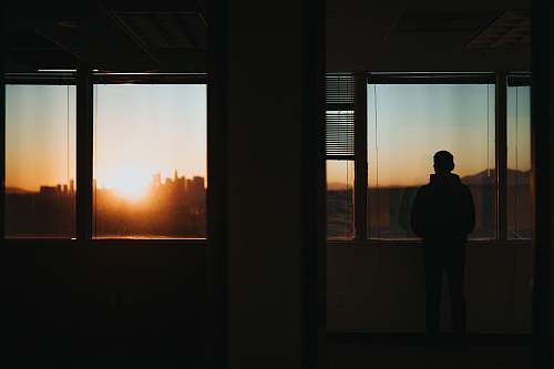 person silhouette of person standing in front of window during golden hour people