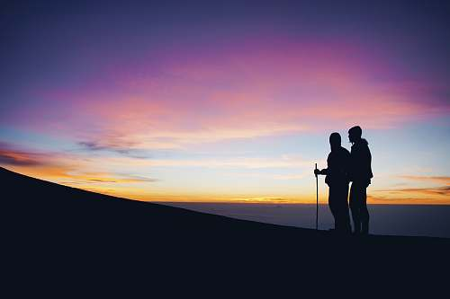 person silhouette of two man walking on top of mountain people