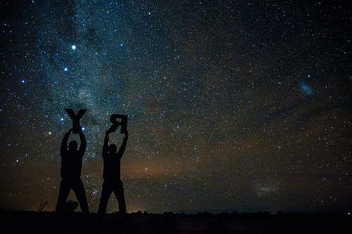 person silhouette of two person holding letters R and Y under starry sky people