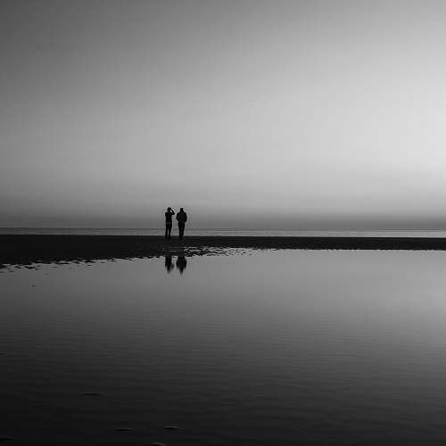 photo person silhouette of two person standing beside calm water black-and-white free for commercial use images