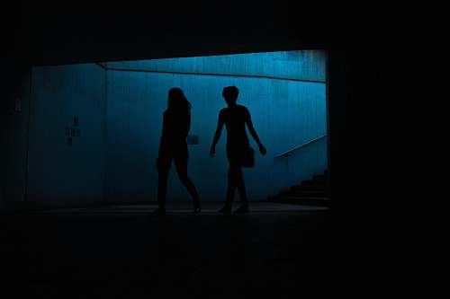 person silhouette of two persons underpass people