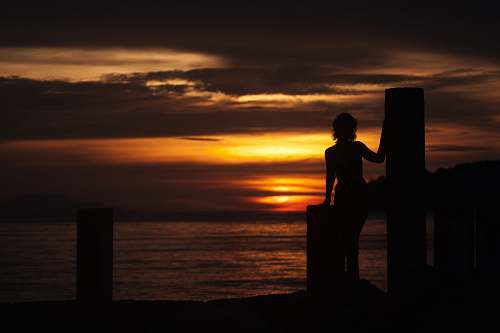 person silhouette of woman on dock during orange sunset people