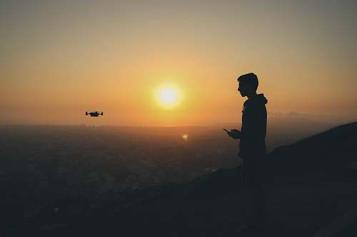 person silhouette photo of man holding drone remote people