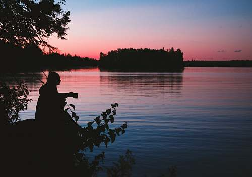 people silhouette photo of man sitting beside body of water person