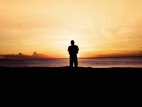 person silhouette photo of person standing in front of body of water during sunset standing