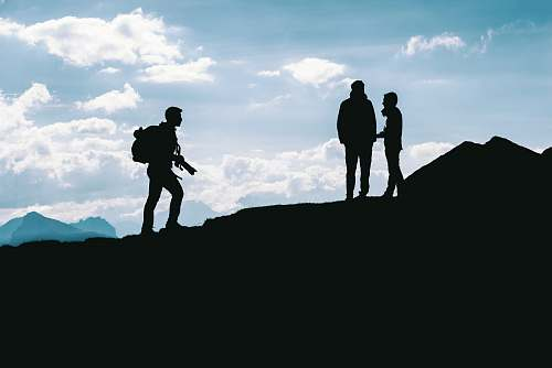 person silhouette photo of three person standing on top of cliff people