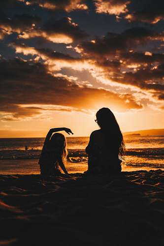 person silhouette photo of woman and girl on shoreline people