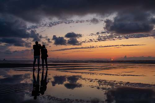 person silhouette photography of man and woman standing on seashore during golden hour nature