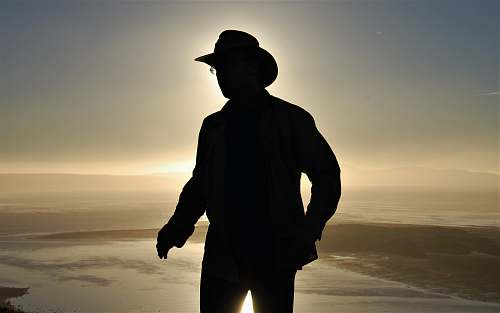 person silhouette photography of man wearing cowboy hat people