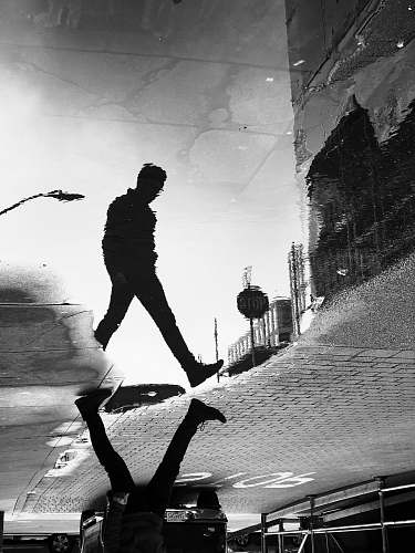 person water reflection shadow of man walking on street in grayscale photography black-and-white