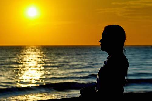 person woman standing infront of beach during sunset people