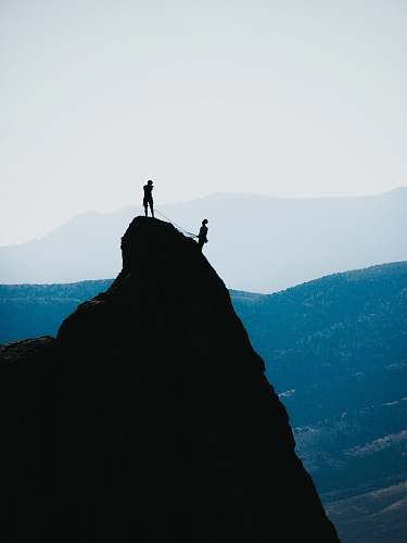 adventure silhouette of two people standing on mountain during daytime outdoors