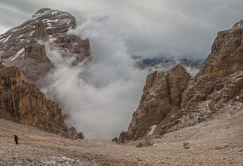 slope landscape photography of foggy mountain rocks descent