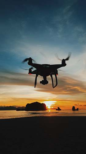 outdoors black drone flying during daytime silhouette
