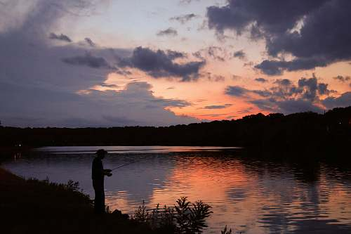 outdoors landscape photo of a fisherman at sunset human