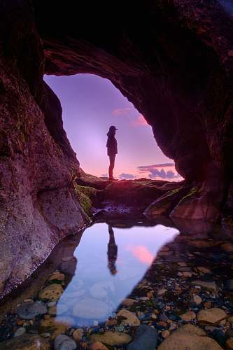 cave man standing in front of cave purple