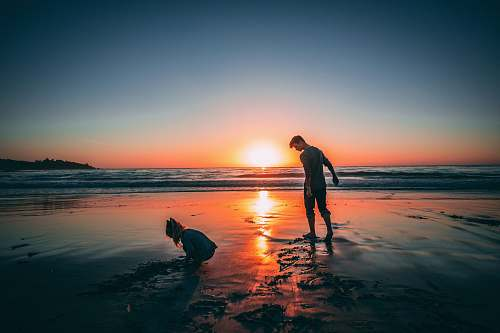 human man standing on beach beside girl playing sand during sunset person