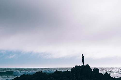 silhouette man standing on boulder in front of ocean standing