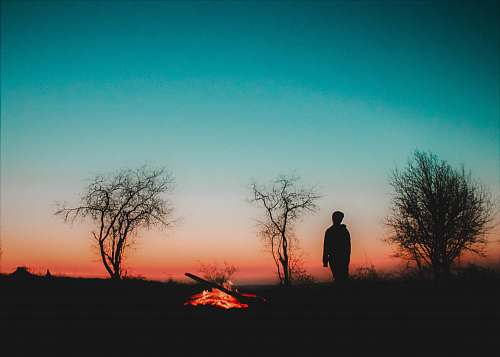 outdoors man standing silhouette near bonfire silhouette