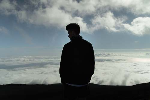 human man standing with sea of clouds in background person