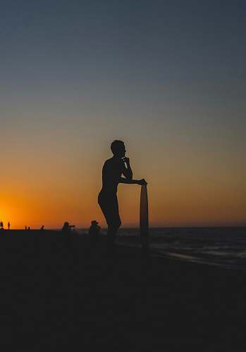 outdoors person standing and holding surfboard on shore during golden hour human