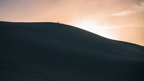 photo desert person walking in dune sand dune free for commercial use images