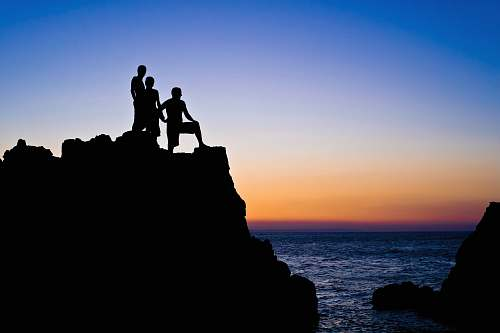 silhouette silhouette of 3 people on top of rocks at beach outdoors