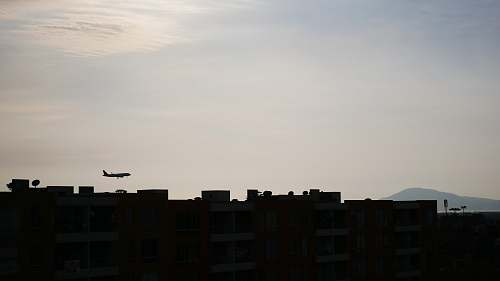 outdoors silhouette of buildings and airplane under white sky silhouette