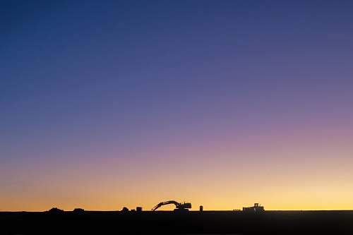 outdoors silhouette of excavator against yellow light sky