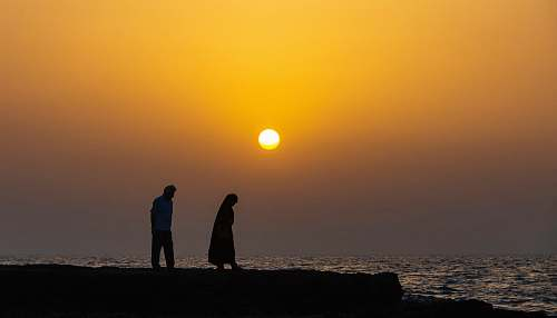 person silhouette of man and woman by the body of water at sunset human