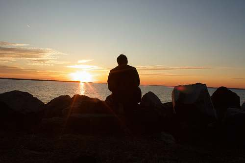 human silhouette of man sitting on rock during sunset person