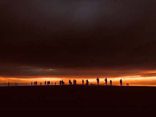 human silhouette of people standing under dark clouds during golden hour person