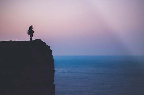 outdoors silhouette of person standing on sea cliff during golden hour cliff