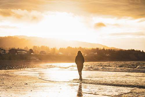 outdoors silhouette of person walking on seashore human