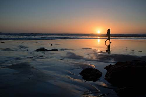 sunset silhouette of person walking on seashore outdoors